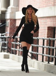 Blake Lively wearing black dress, boots and a big hat